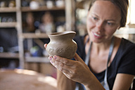 Smiling potter in workshop looking at earthenware jar - KNTF000361