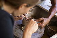 Man and woman in workshop working on pottery - KNTF000370