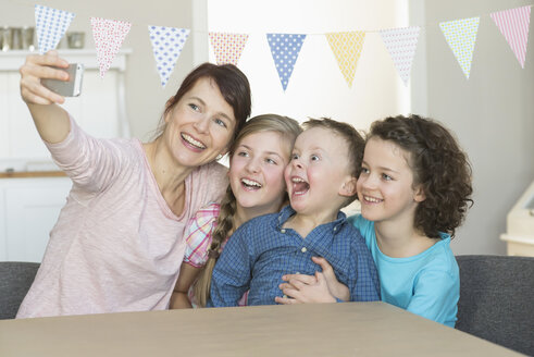 Happy mother with three children taking a selfie - NHF001494