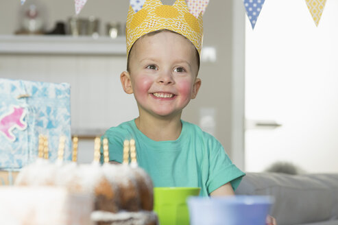 Happy boy wearing paper crown sitting at birthday table - NHF001500
