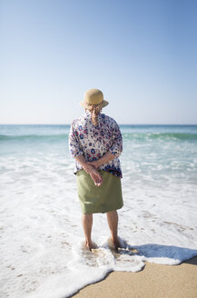 Back view of senior woman standing on the beach - RAEF001221