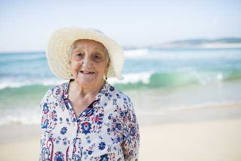 Portrait of smiling senior woman standing on the beach - RAEF001224