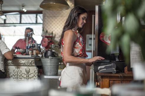 Waitress working, using till in restaurant - ZEF008721