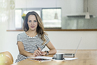 Portrait of confident woman with laptop at table - SBOF000074