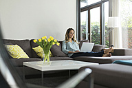 Woman at home sitting on couch using laptop - SBOF000092