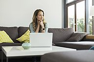 Woman at home sitting on couch with laptop - SBOF000095