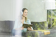 Smiling woman at home on couch with digital tablet and headphones - SBOF000098