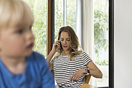 Mother on cell phone and son in foreground - SBOF000107