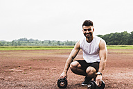 Portrait of smiling athlete with dumbbells on sports field - UUF007709