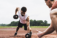Athlete exercising with dumbbells on sports field supported by his training partner - UUF007715