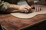 Luthier manufacturing a guitar in his workshop, close-up - ABZF000700