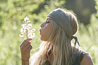 Blond woman blowing seeds of an umbel into the air - TCF004976