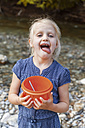Portrait of blond girl with plastic bowl licking her lips - TCF005000