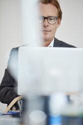 Portrait of businessman working with laptop - RHF001607