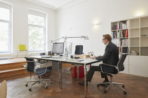 Businessman working with notebook in an office - RHF001616
