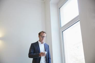 Businessman standing beside window looking at his smartphone - RHF001622
