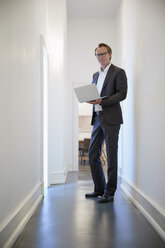 Portrait of smiling businessman with notebook standing in corridor - RHF001625