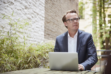 Businessman sitting with laptop at table in a backyard - RHF001628