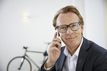 Portrait of smiling businessman telephoning with smartphone - RHF001637