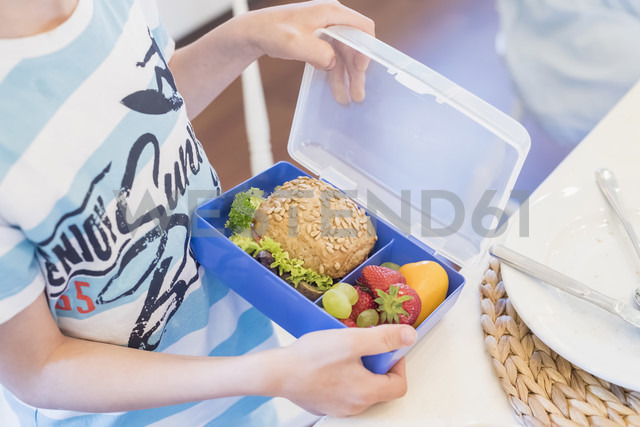 Boy packing lunch box with healthy food - MJF001854