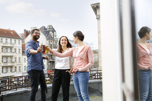 Man and two women clinking bottles on roof terrace - FKF001872