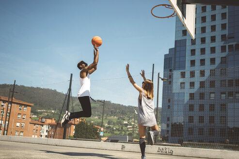 Young couple playing basketball on court - DAPF000158