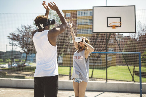 Young couple playing basketball with virtual reality glasses on - DAPF000167