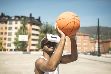 Young man playing basketball with virtual reality glasses on - DAPF000170