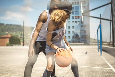 Young couple playing basketball on court - DAPF000179