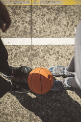 Young man and woman standing on basketball field with between their feet - DAPF000185