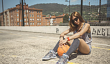 Young woman sitting on ground of baketball court with ball between her legs - DAPF000191
