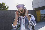 Bearded young man with sunglasses listening music with headphones - FMOF000020