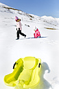Spain, Asturias, kids playing in a snow, sledge in the foreground - MGOF001967