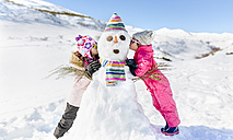 Spain, Asturias, kids playing with snowmen, kissing - MGOF001982