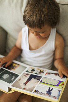 Little boy sitting on the couch watching a photo album - VABF000574