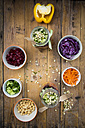 Two glasses of rainbow salad with chick-peas, sprouts and different vegetables and bowls with ingredients - LVF004972