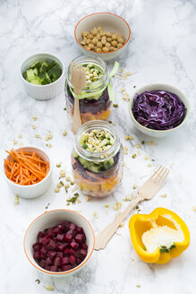 Two glasses of rainbow salad with chick-peas, sprouts and different vegetables and bowls with ingredients - LVF004978