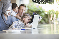 Family sitting on terrace looking together at laptop - ZEF008744