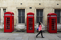 United Kingdom, London, Unfocused woman walking, telephone booths in the background - ABZ000716