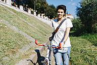 Smiling young woman pushing bicycle - GIOF001219