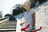 Smiling young woman with bicycle in backlight - GIOF001222