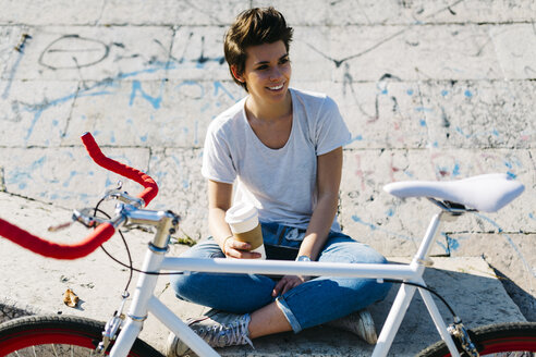 Smiling young woman with bicycle and coffee to go - GIOF001225