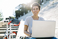 Young woman with bicycle sitting outdoors using laptop - GIOF001228