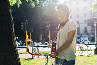 Young woman with bicycle in park - GIOF001243