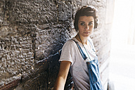 Young woman at stone wall wearing headphones - GIOF001249