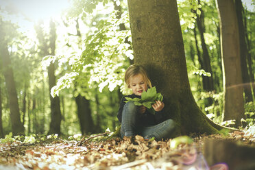 Girl in forest examining leaves - SBOF000152
