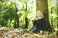 Girl in forest blowing blowball - SBOF000155