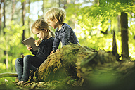 Brother and sister in forest using digital tablet - SBOF000164