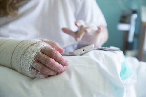 Woman in the hospital, operated hand, using mobile phone, left hand - ERLF000179