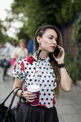 Portrait of young woman with coffee to go telephoning with smartphone - MAUF000664